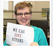 "Special needs student holding up paper with ""We can love others"" written on it."