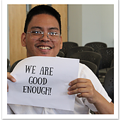 "Special needs student holding up paper with ""We are good enough!!"" written on it."