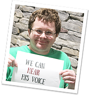 "Special needs student holding up paper with ""We can hear his voice"" written on it."